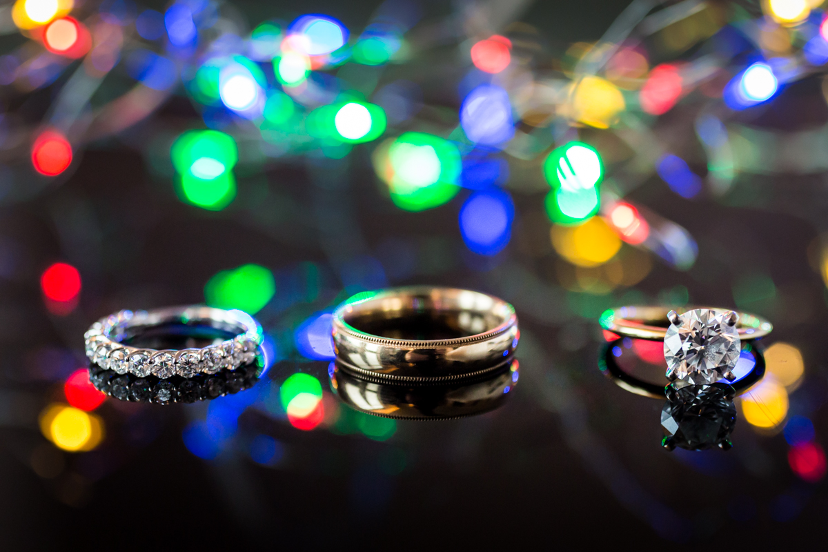Wedding rings and engagement ring in front of colored lights