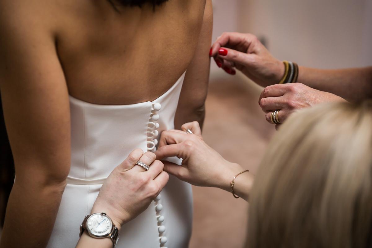 Hands closing buttons on a bride's wedding dress
