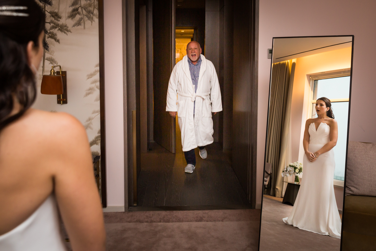 Father wearing robe seeing bride in wedding dress for the first time