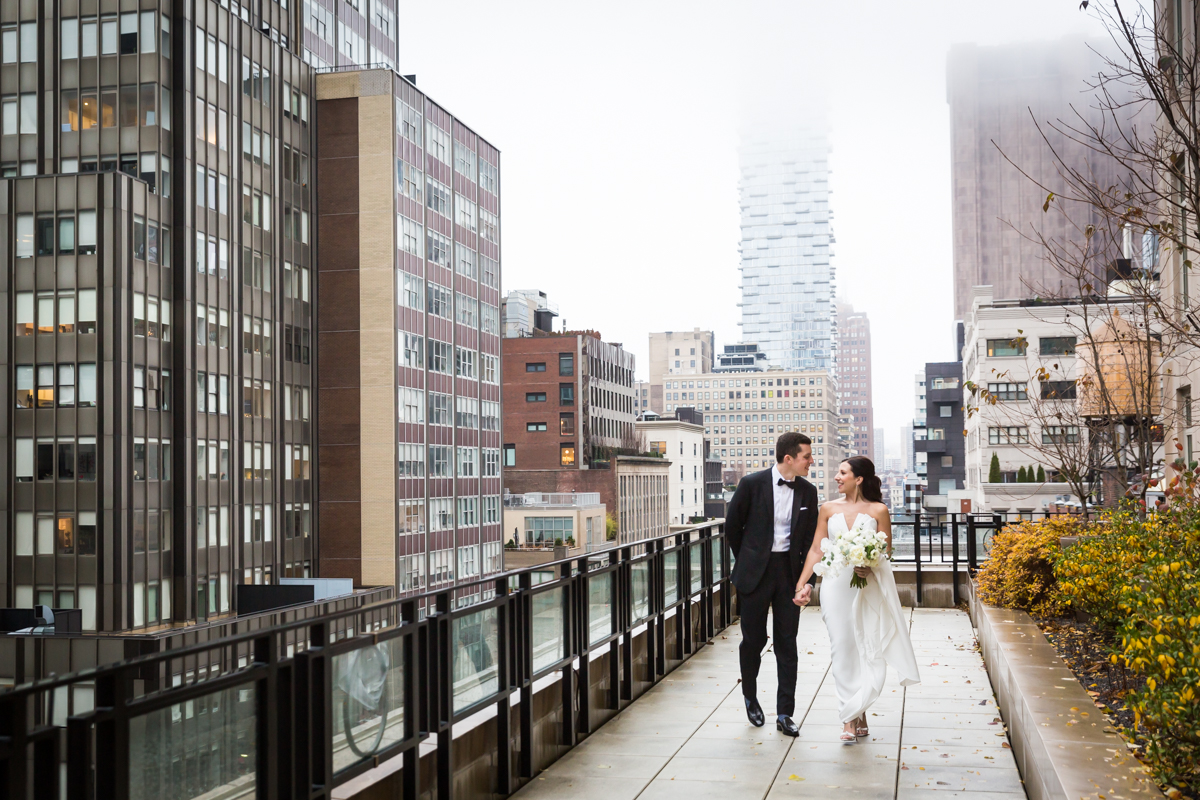 Bride and groom walking on terrace at Four Seasons Hotel New York Downtown
