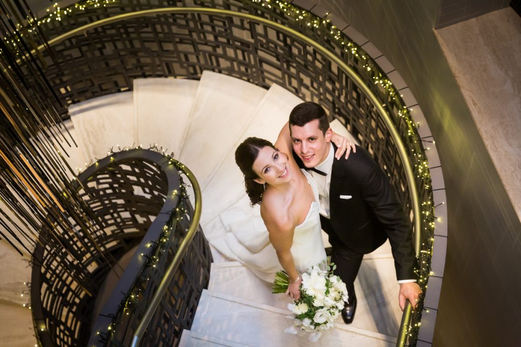 Bride and groom looking up on staircase