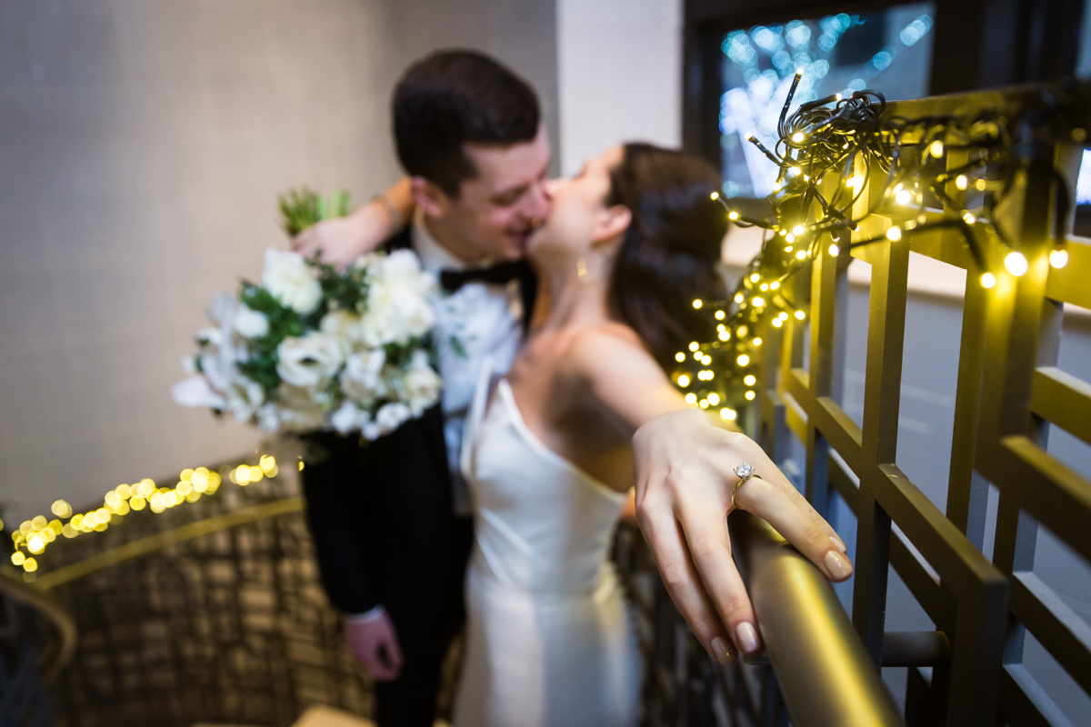 Outstretched hand of bride in front of bride and groom kissing