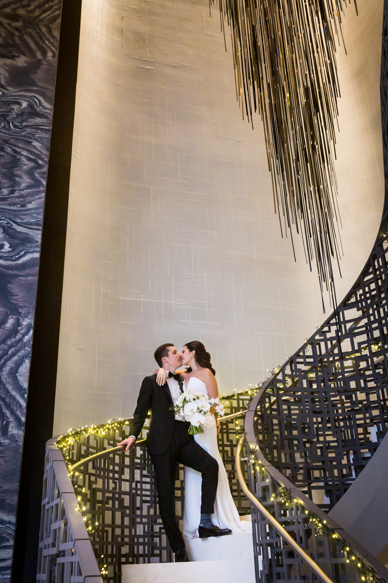 Bride and groom posed at the base of the staircase at the Four Seasons Hotel New York Downtown