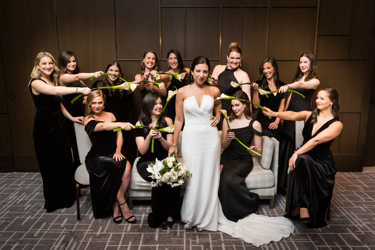 Funny portrait bridesmaids pointing bouquets at bride