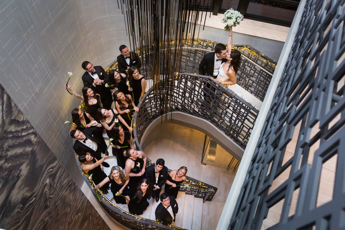 Bridal party celebrating as bride and groom kiss on the Four Seasons Hotel New York Downtown staircase