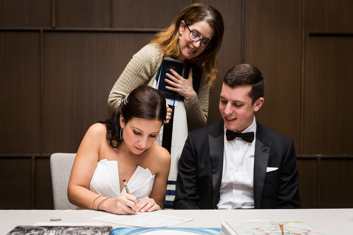 Cantor watching bride signing ketubah at a Four Seasons Hotel New York Downtown wedding