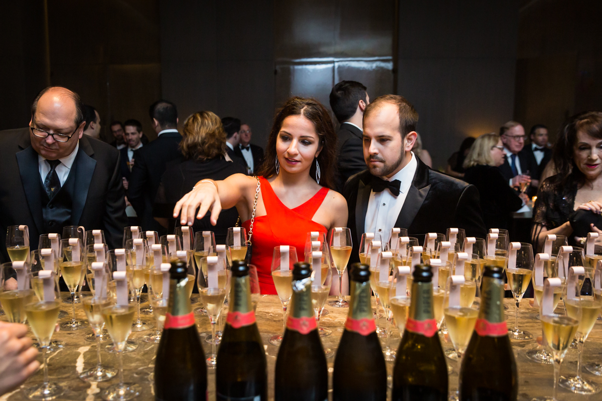 Guests selecting champagne flute with attached escort card