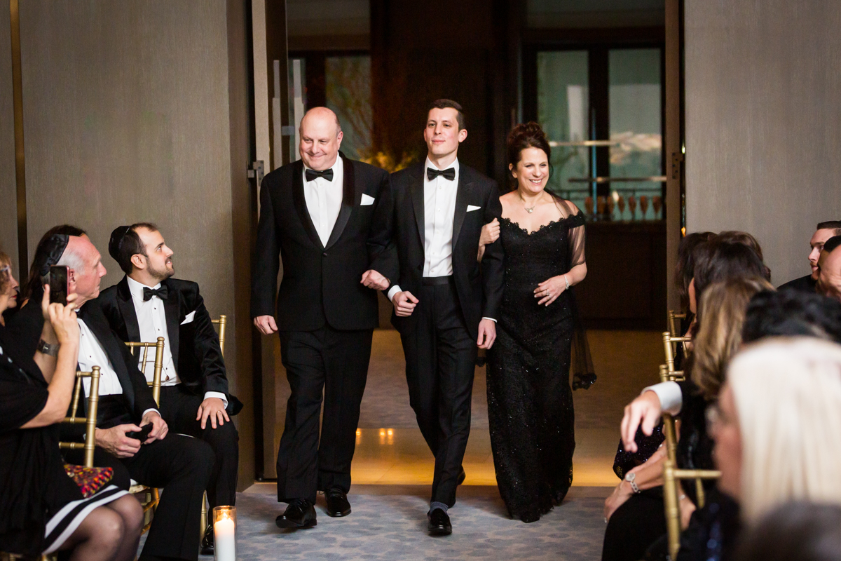Groom and parents walking down the aisle at a Four Seasons Hotel New York Downtown wedding