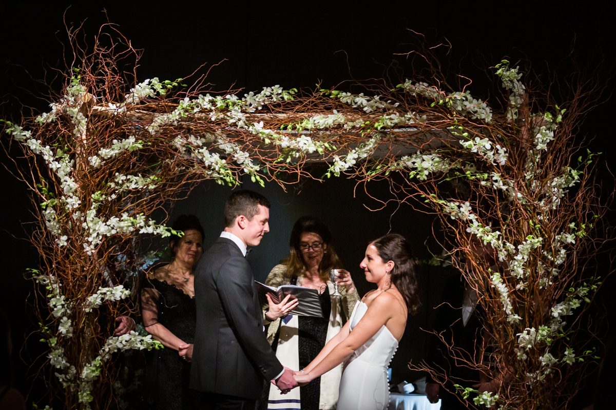 Bride and groom holding hands under chuppah at a Four Seasons Hotel New York Downtown wedding