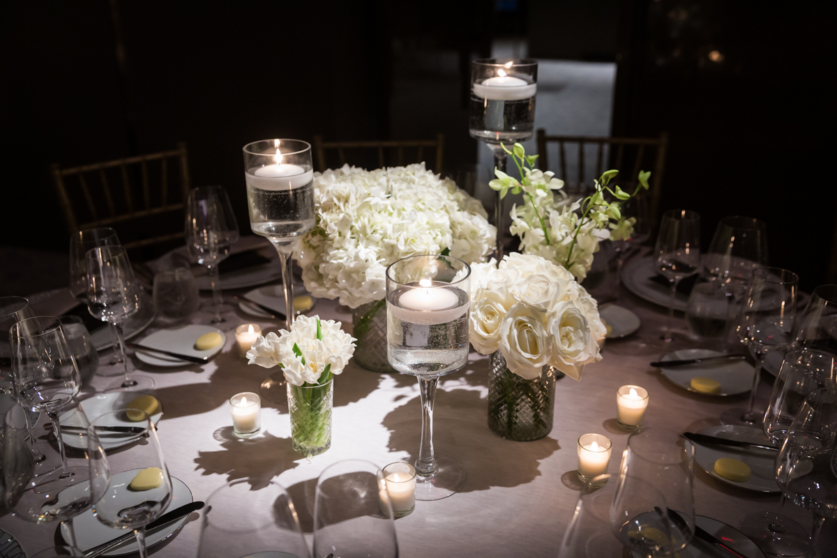 White floral centerpieces and candles at a Four Seasons Hotel New York Downtown wedding
