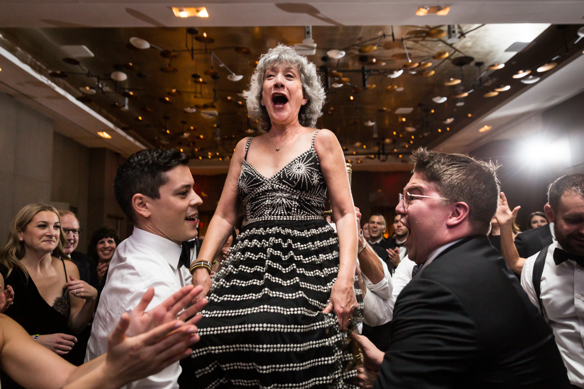 Mother of the bride lifted in a chair during hora dance at a Four Seasons Hotel New York Downtown wedding