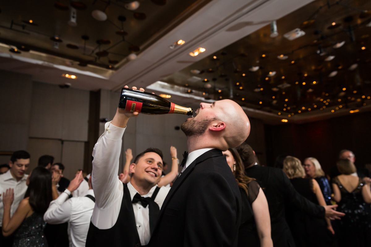 Guest pouring champagne in the mouth of another guest at a Four Seasons Hotel New York Downtown wedding
