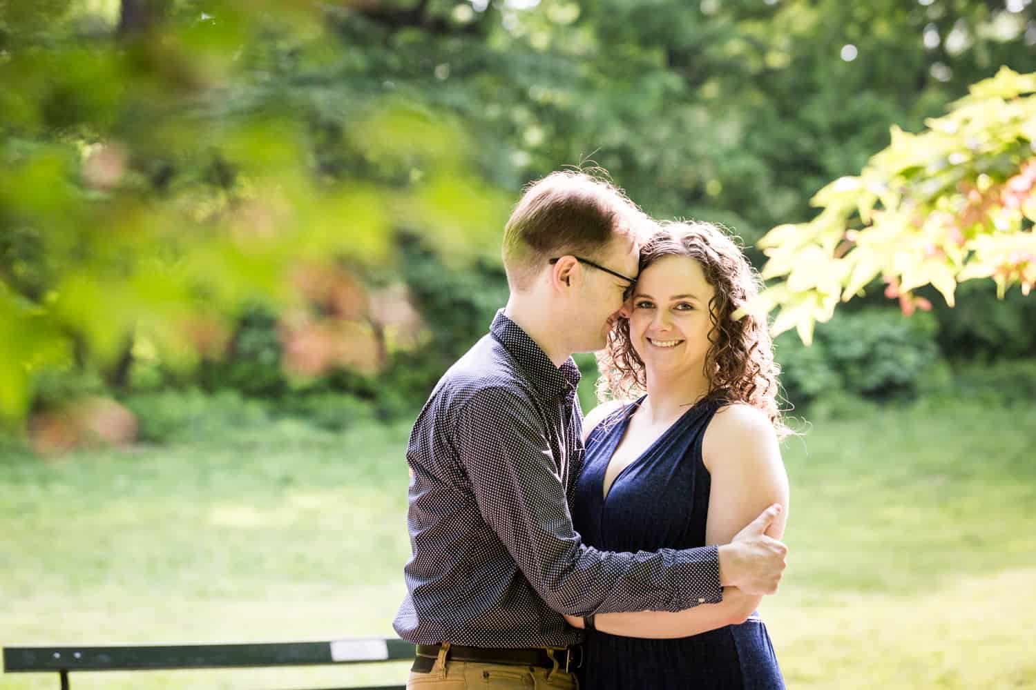 Couple cuddling in Central Park for Shakespeare Garden engagement photos
