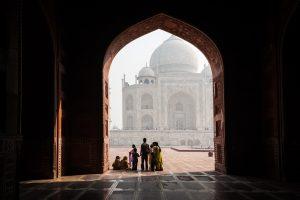 Family standing in shadow of Taj Mahal