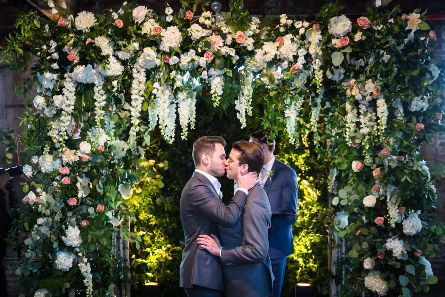 Greenpoint Loft wedding photos of two grooms kissing under gigantic floral altarpiece