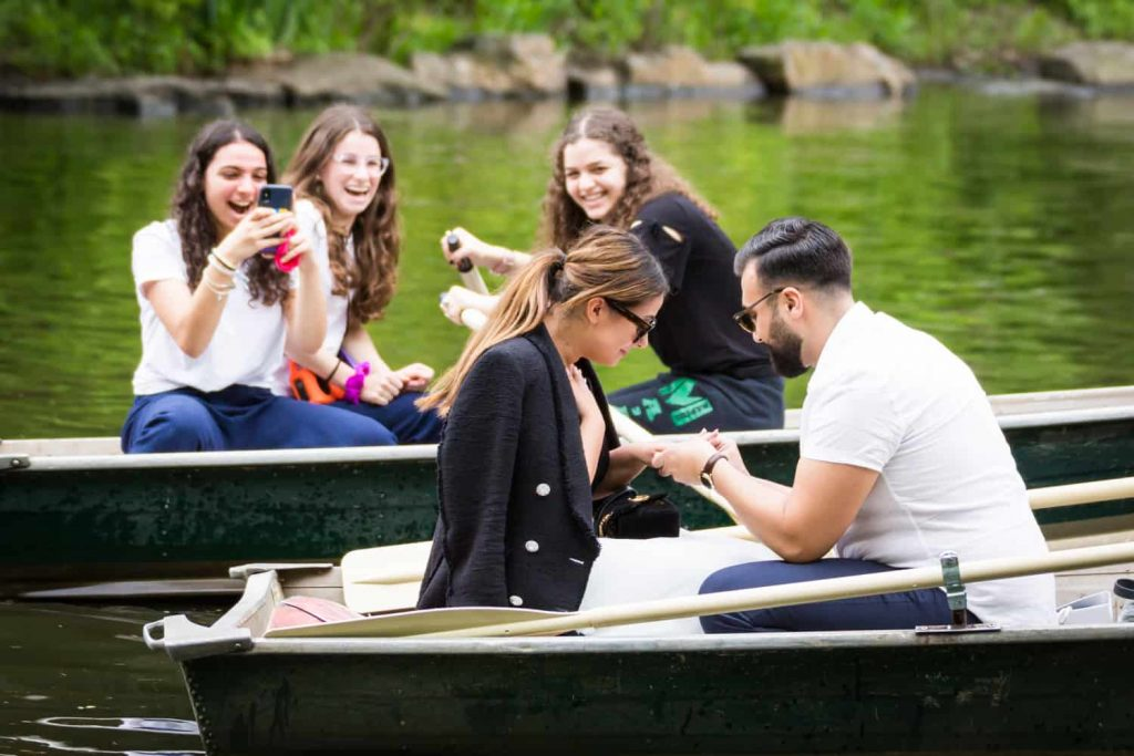 Three girls watching man propose to woman in boat at a surprise proposal on Central Park Lake