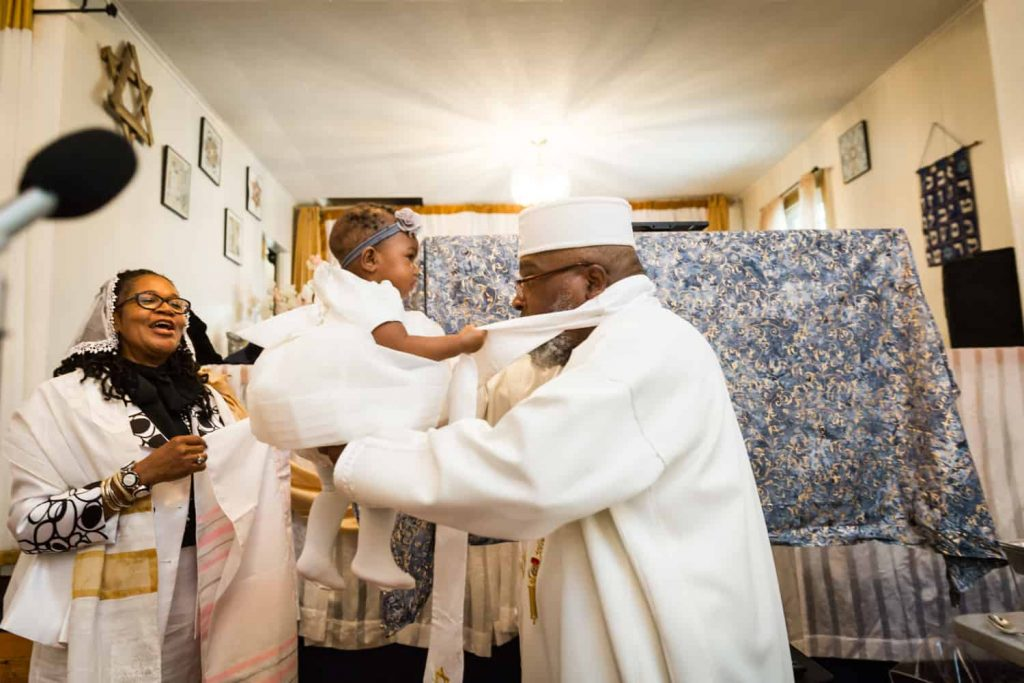 Pastor holding little girl up to the light during Jamaica christening