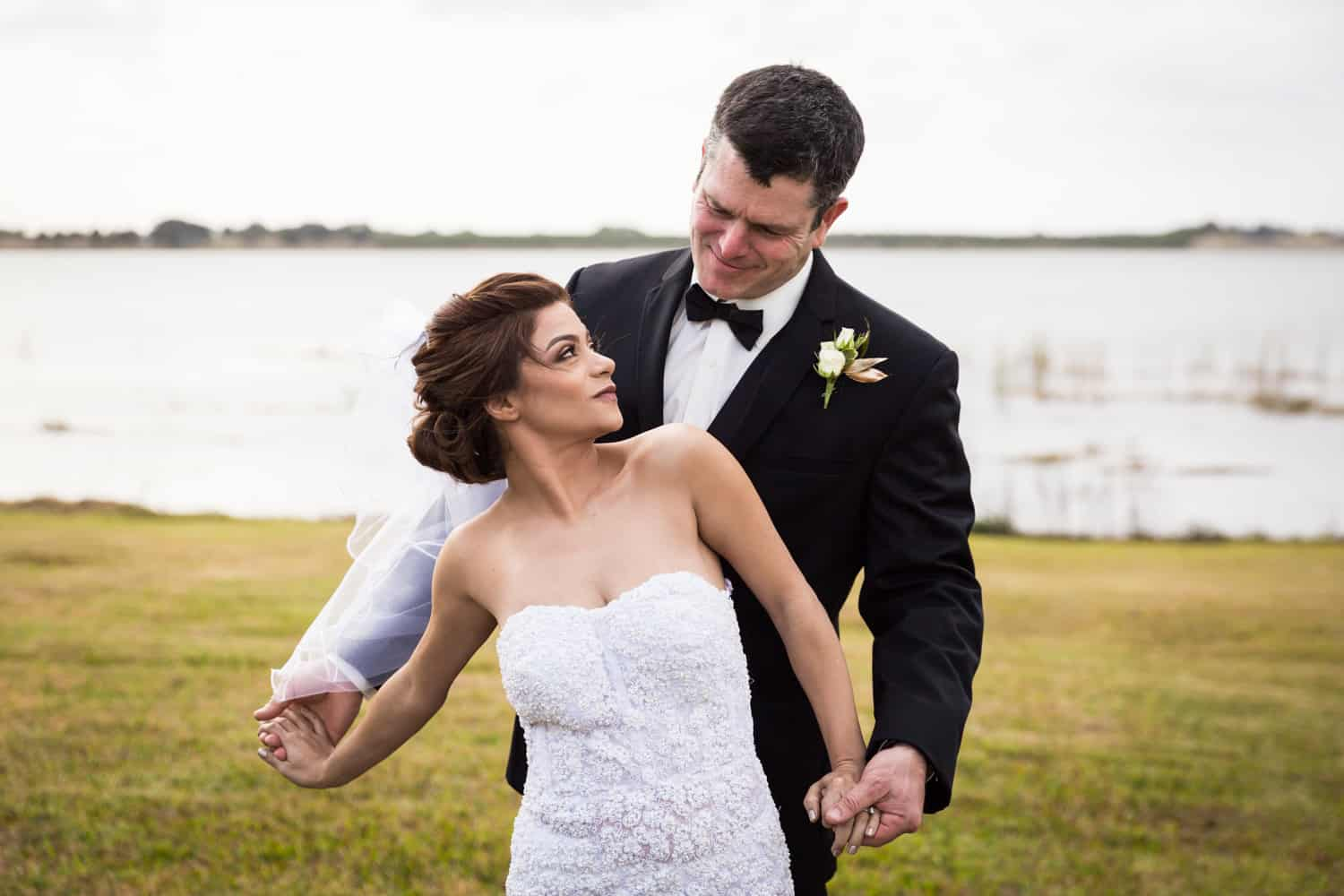 Bride and groom holding hands in front of lake for an article on wedding cost cutting tips