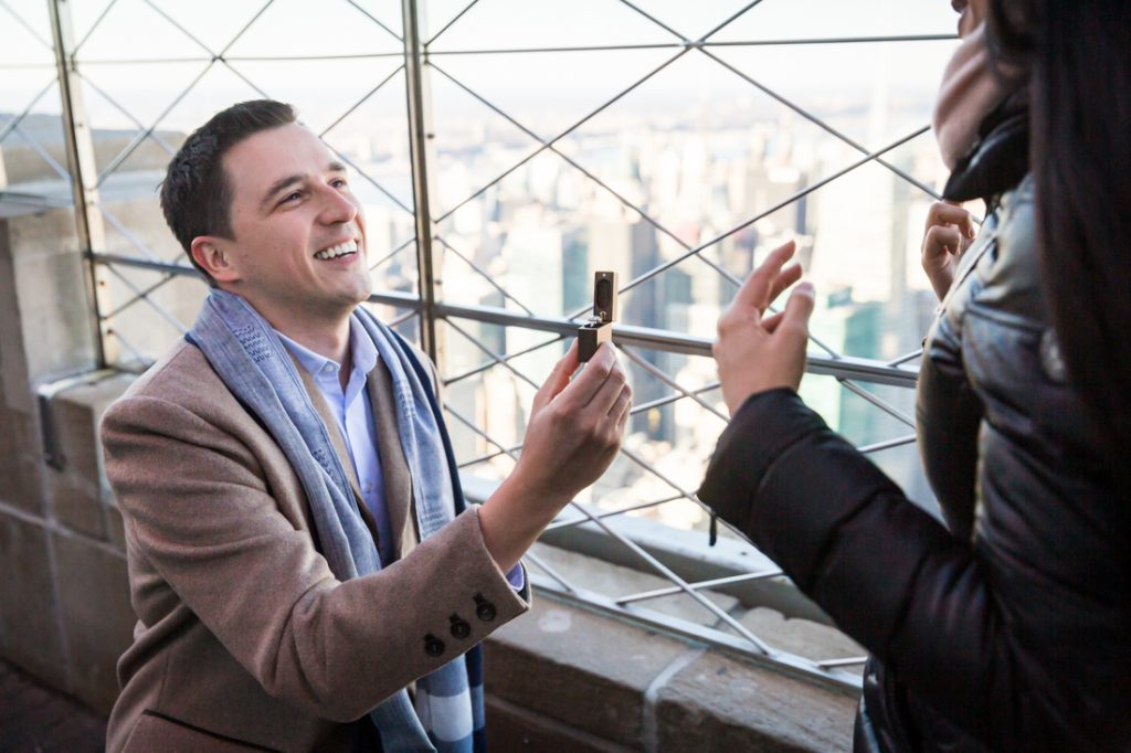 Man on one knee holding ring making a proposal on top of the Empire State Building