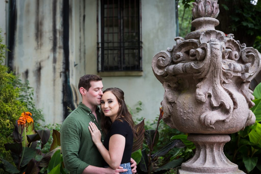 Vanderbilt Museum engagement photos of man kissing woman on side of head with stone urn