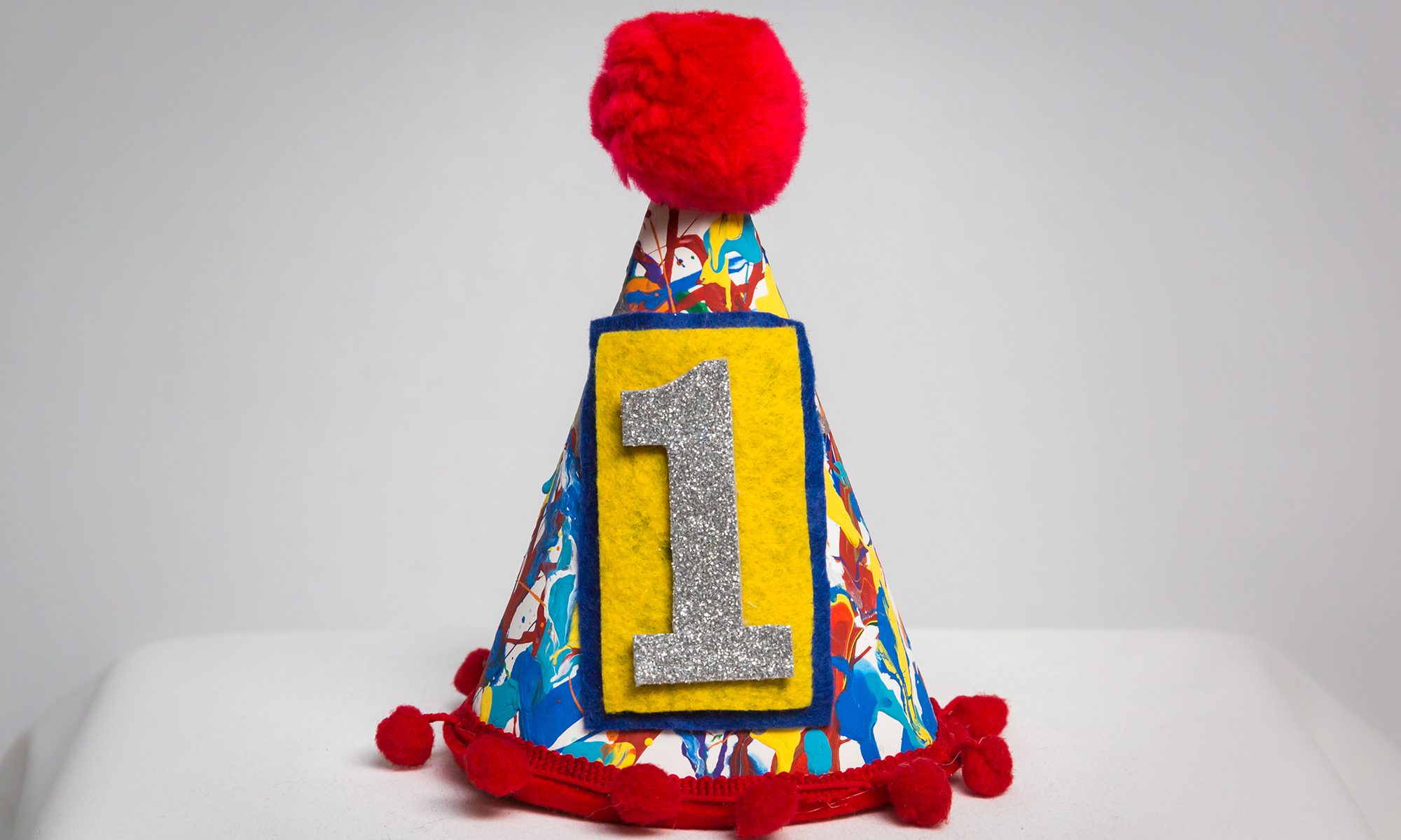 Child's first birthday party hat with red pom pom