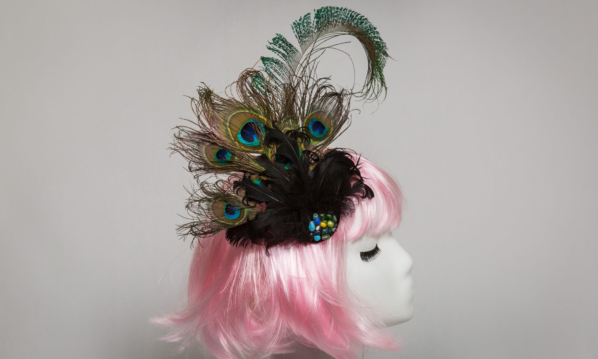Pink-haired mannequin wearing peacock feather bridal fascinator