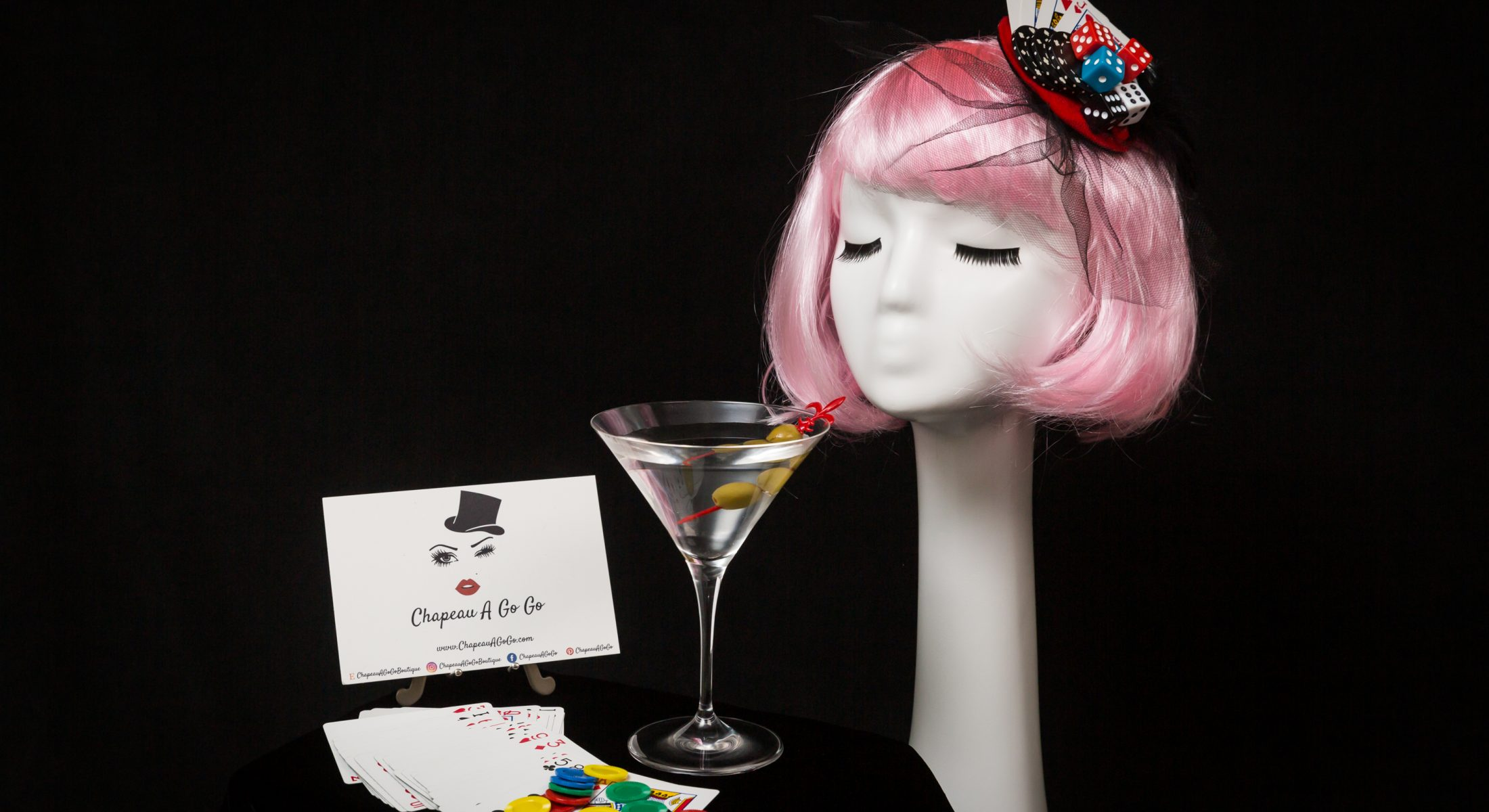Las Vegas fascinator by Chapeau A Go Go on pink haired mannequin with martini glass