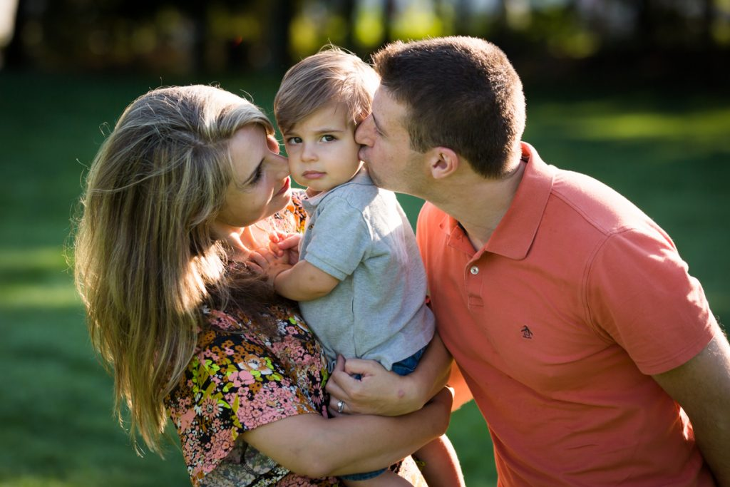 Parents kissing boy on cheeks during a Chelsea Waterside Park family portrait session