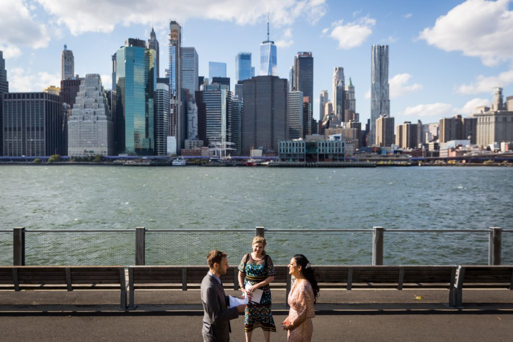 Couple saying vows in front of NYC waterfront for an article on how to get married in Brooklyn Bridge Park