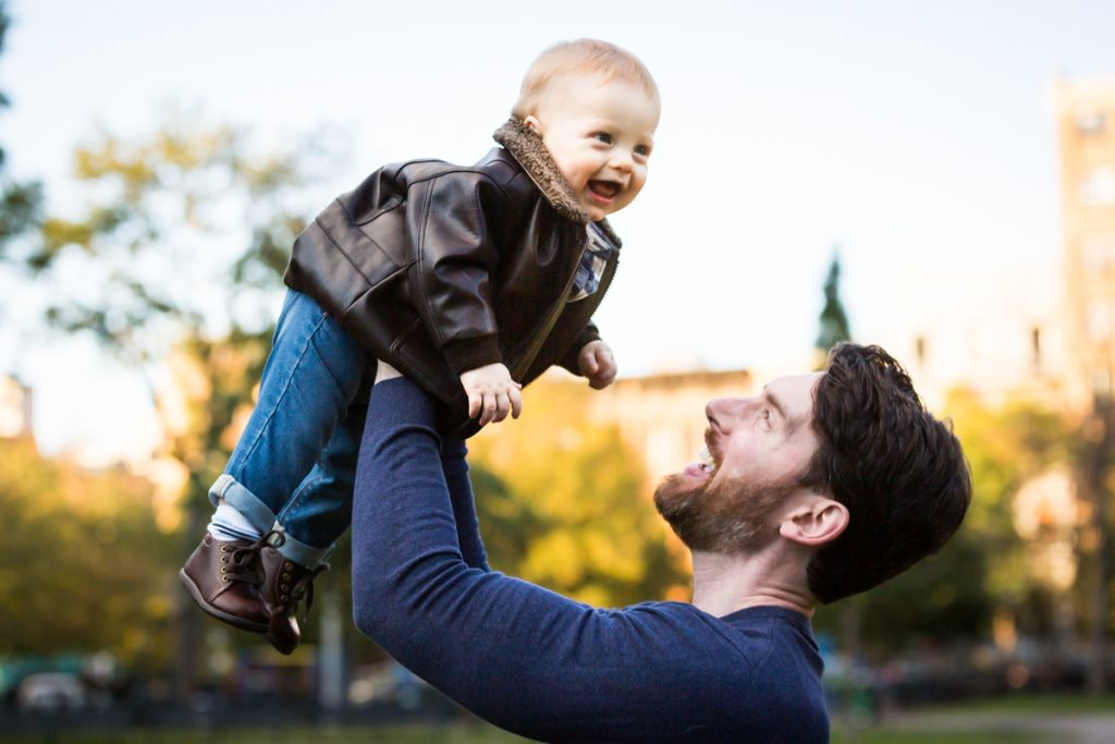 Father lifting baby in the air during a Marcus Garvey Park family portrait session