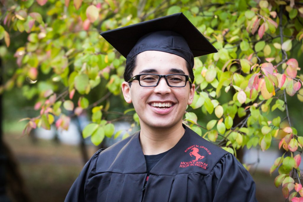 Young man wearing graduation cap and gown during a Central Park senior portrait session