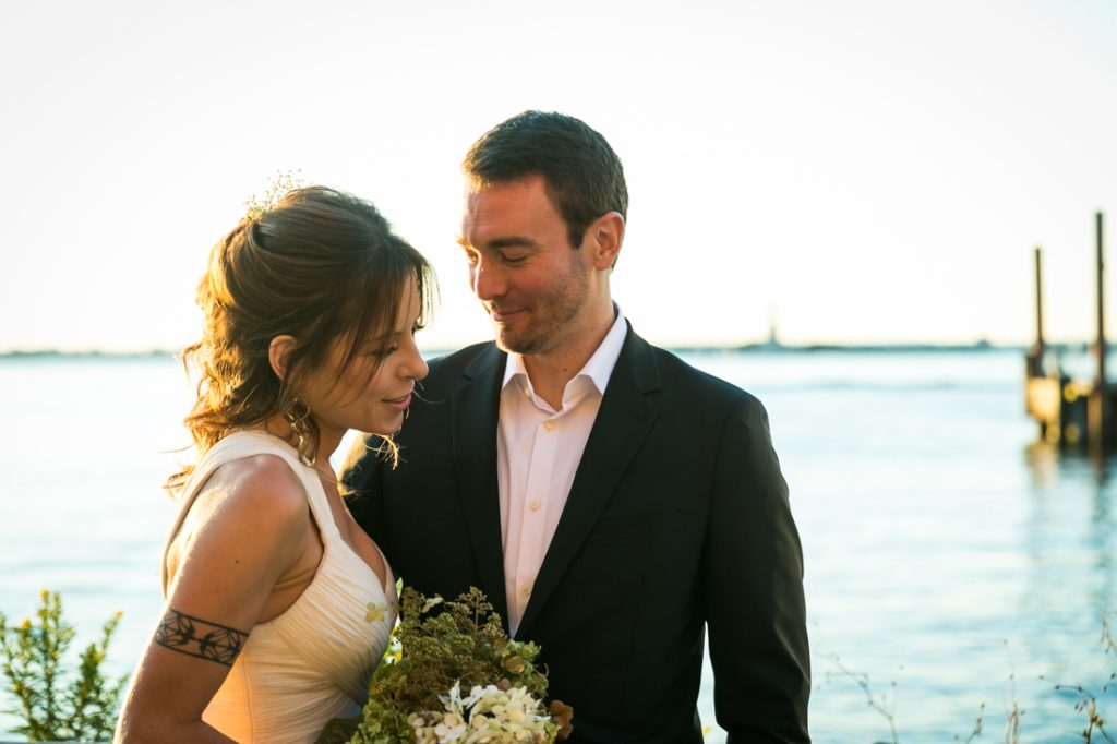 Bride and groom on Red Hook pier at sunset