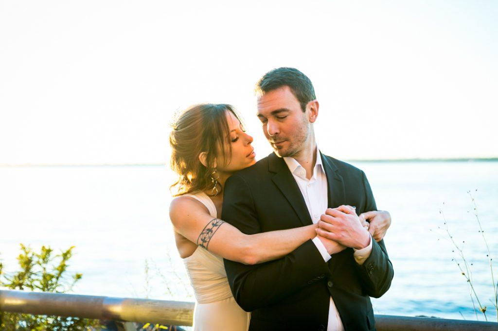 Bride hugging groom on Red Hook pier at sunset