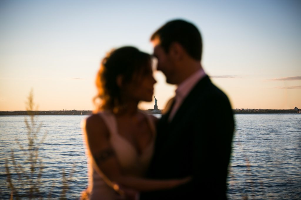 Bride and groom on Red Hook pier at sunset with Statue of Liberty in background