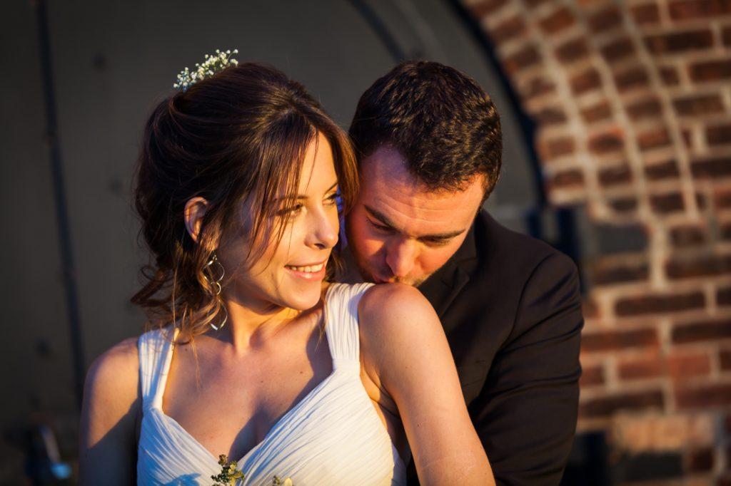 Groom kissing bride's shoulder on Red Hook pier