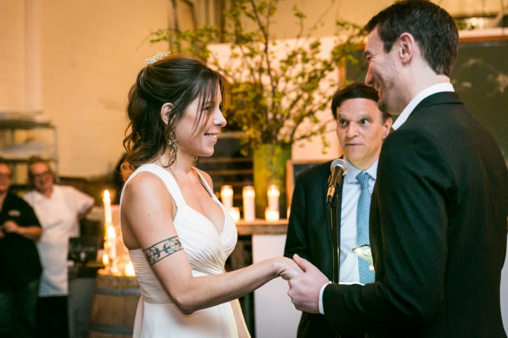 Groom holding bride's hand during ceremony at an Atelier Roquette wedding