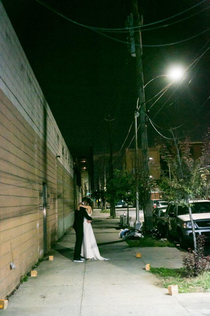 Bride and groom hugging against wall