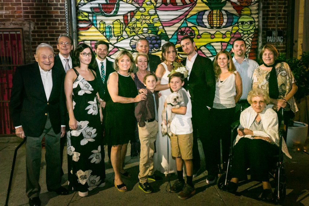 Group portrait of guests in front of graffiti