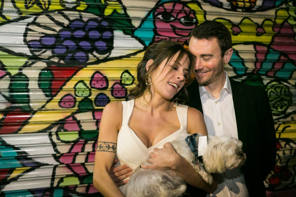 Bride and groom holding dog in front of graffiti