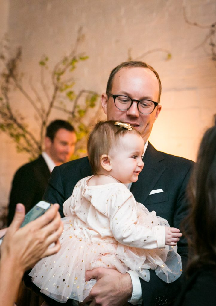 Man holding smiling baby at an Atelier Roquette wedding