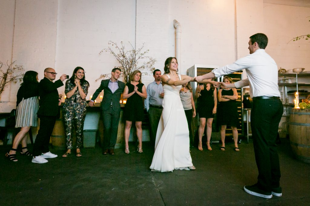 Bride and groom dancing with arms outstretched