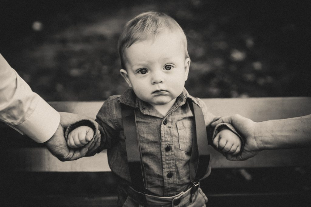 Black and white photo of little boy being held by arms