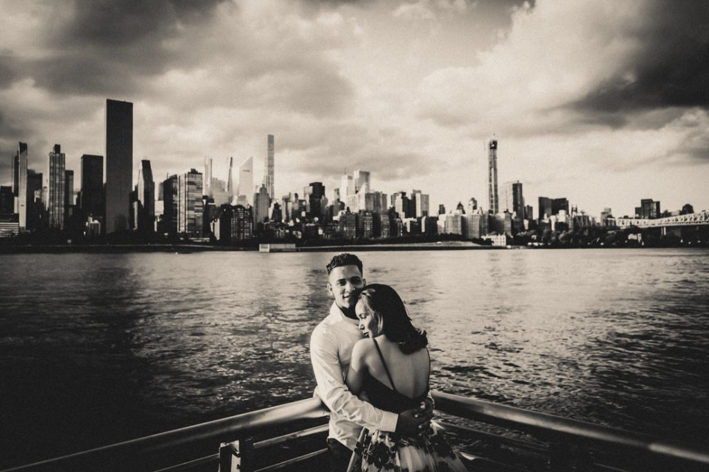 Black and white photo of engaged couple hugging in front of NYC skyline
