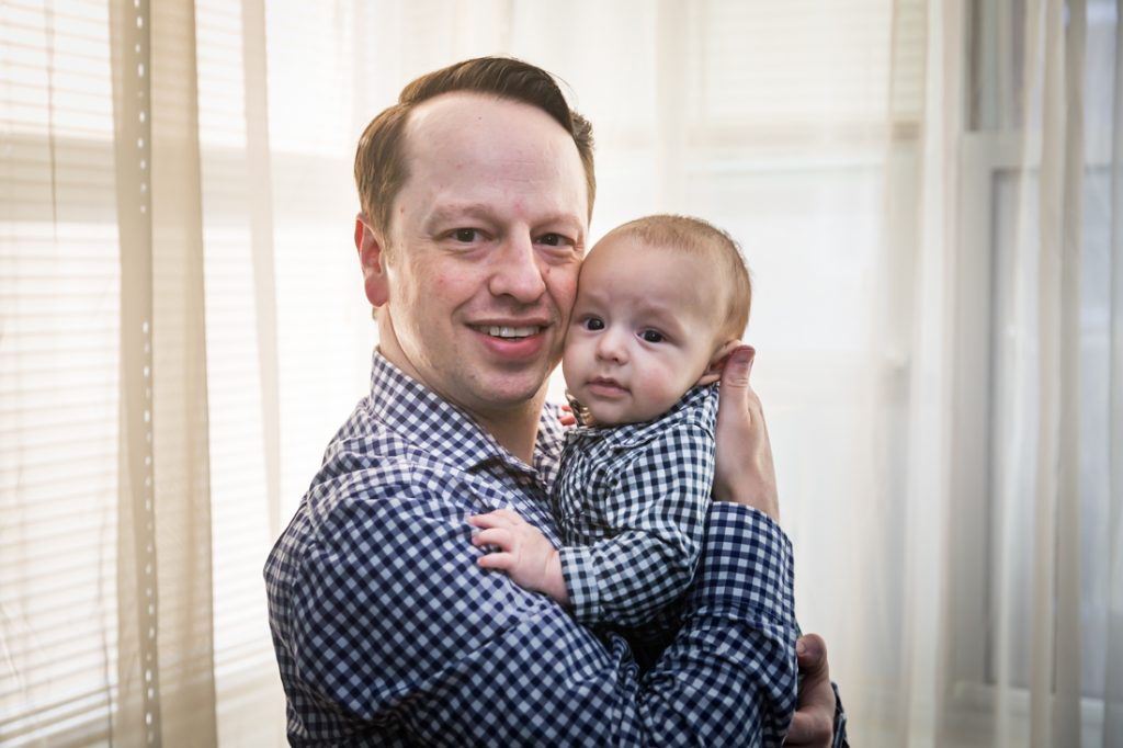Father holding baby boy in front of window for Forest Hills baby portrait