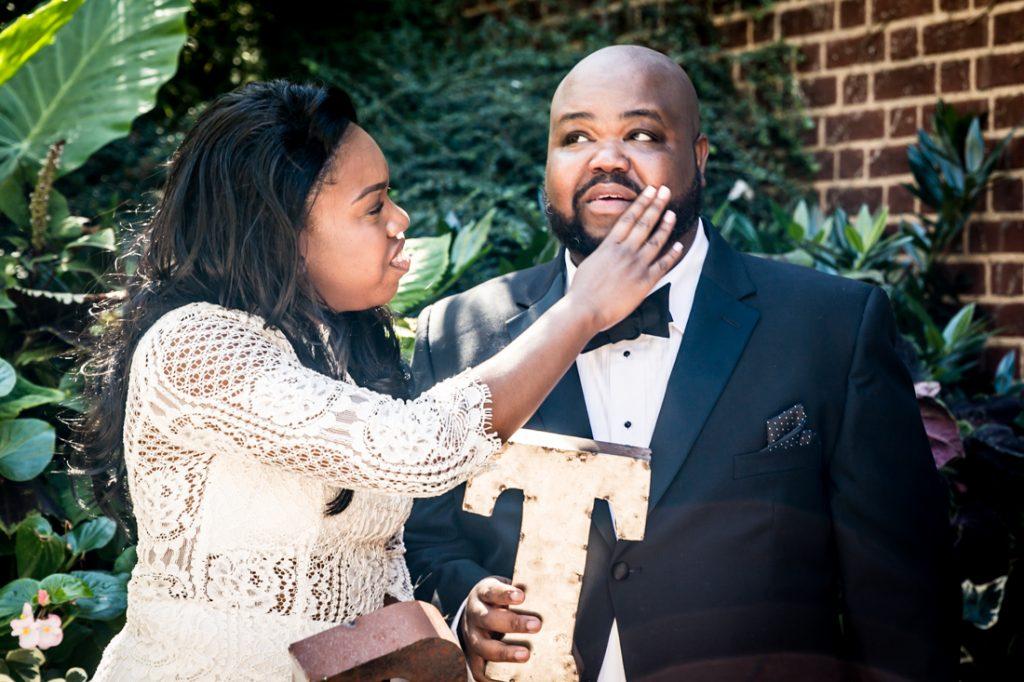 Bride brushing lipstick off of groom before a Kew Gardens wedding