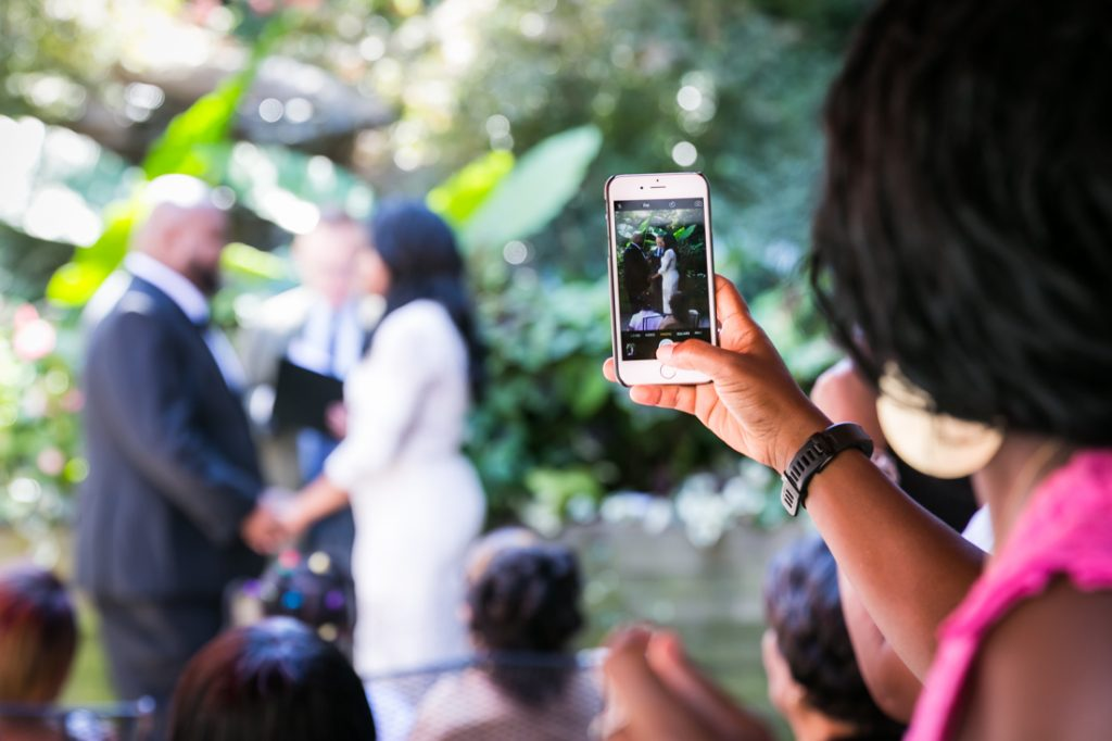Guest taking photo of bride and groom with cell phone