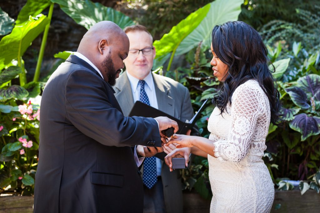 Groom putting ring on bride at a Kew Gardens wedding