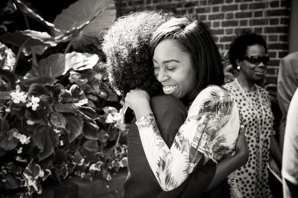 Black and white photo of two female guests hugging