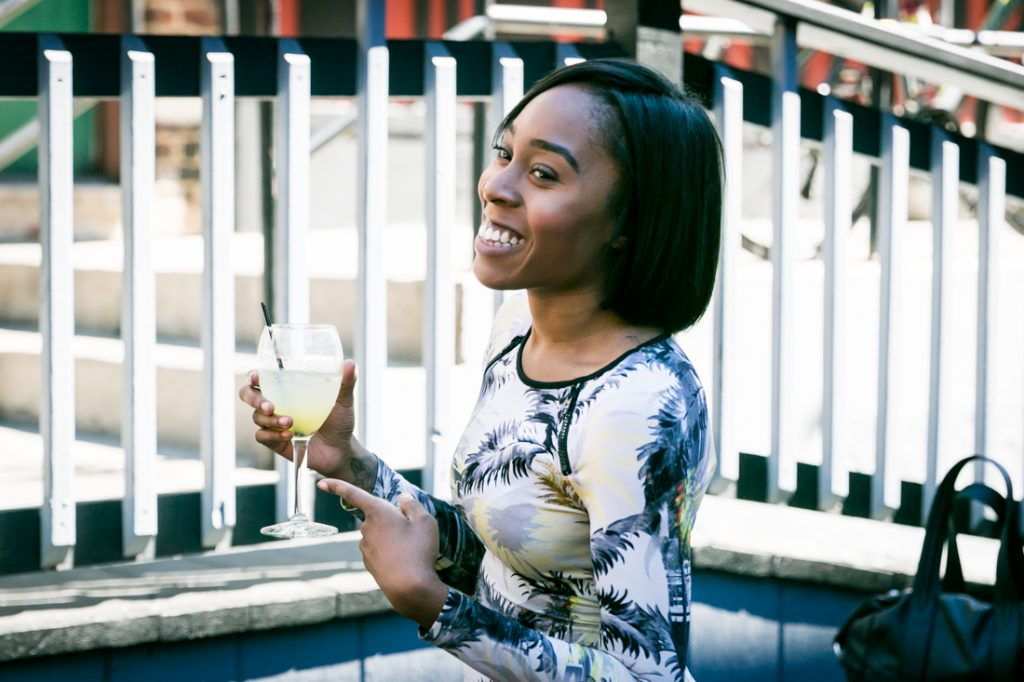 Female guest smiling and holding cocktail in hand