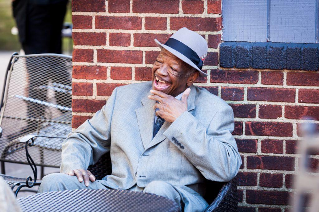 Older gentleman wearing hat and laughing at a Kew Gardens wedding